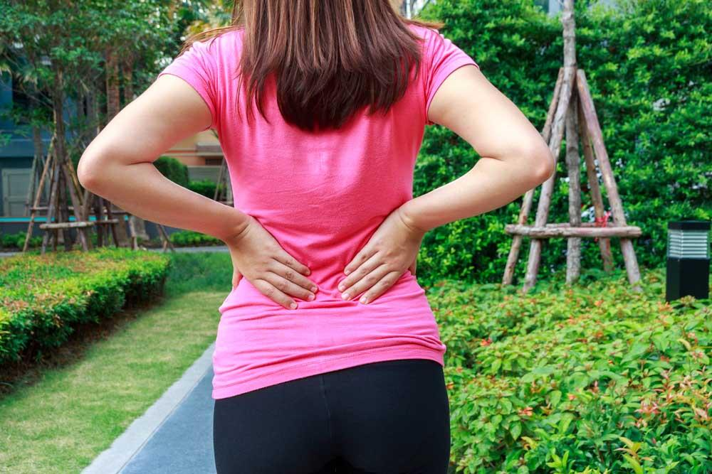 Woman with back pain walking through her garden.